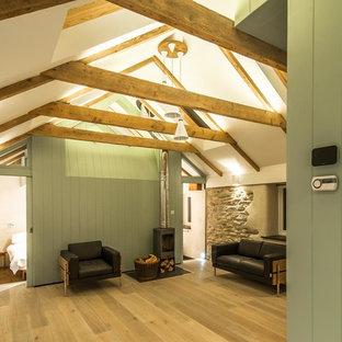 Ispirazione per un piccolo soggiorno minimal con pareti bianche, parquet chiaro, stufa a legna e cornice del camino in metallo
