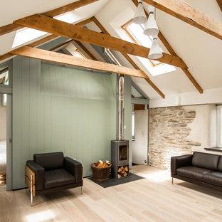 Foto på ett litet funkis loftrum, med ett finrum, vita väggar, ljust trägolv och en öppen vedspis