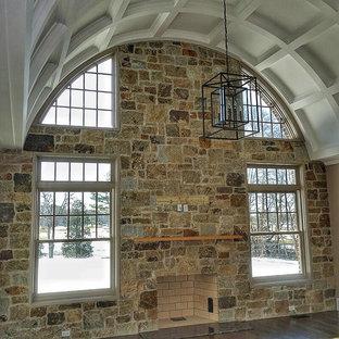 他の地域のトラディショナルスタイルのおしゃれなLDK (マルチカラーの壁、濃色無垢フローリング、標準型暖炉、石材の暖炉まわり、茶色い床、テレビなし) の写真