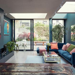 Inspiration för eklektiska vardagsrum, med blå väggar, en bred öppen spis och grått golv