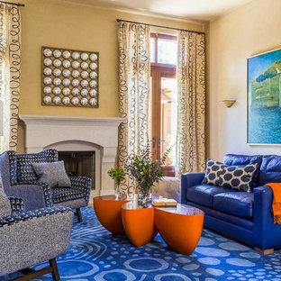 Foto di un grande soggiorno bohémian aperto con pareti gialle, camino classico, cornice del camino in cemento, sala formale, moquette e pavimento blu