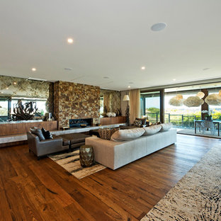 This is an example of a contemporary open concept living room in Melbourne with white walls, medium hardwood floors, a ribbon fireplace, a stone fireplace surround and brown floor.