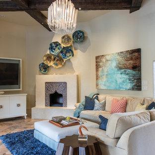 ダラスの大きい地中海スタイルのおしゃれなLDK (ベージュの壁、トラバーチンの床、コーナー設置型暖炉、タイルの暖炉まわり、壁掛け型テレビ) の写真