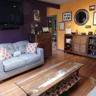 Immagine di un piccolo soggiorno bohémian chiuso con sala formale, pareti multicolore, pavimento in legno massello medio, camino bifacciale, cornice del camino in pietra e TV a parete