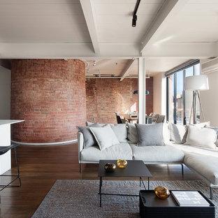 Modelo de salón abierto, contemporáneo, de tamaño medio, sin chimenea, con paredes blancas y suelo de madera oscura