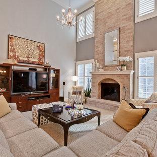 Klassisk inredning av ett mellanstort allrum med öppen planlösning, med grå väggar, heltäckningsmatta, en standard öppen spis, en spiselkrans i tegelsten och en fristående TV