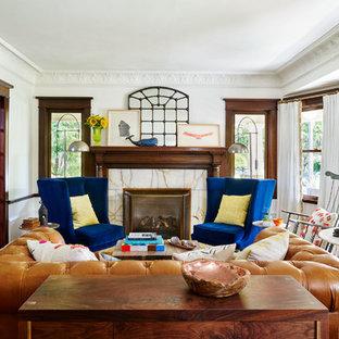 Immagine di un soggiorno boho chic di medie dimensioni e chiuso con pareti bianche, pavimento in legno massello medio, camino classico, cornice del camino in pietra e sala formale