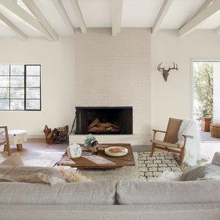 Exemple d'un grand salon sud-ouest américain avec un mur blanc, une cheminée standard, un manteau de cheminée en brique et aucun téléviseur.