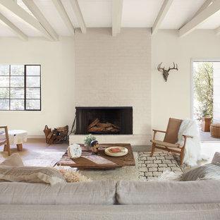 ロサンゼルスの広いサンタフェスタイルのおしゃれなLDK (フォーマル、ベージュの壁、濃色無垢フローリング、標準型暖炉、レンガの暖炉まわり、テレビなし、茶色い床) の写真