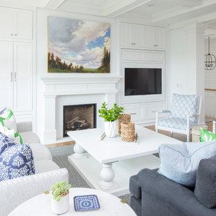 Foto di un grande soggiorno tradizionale aperto con sala formale, pareti bianche, pavimento in legno massello medio, camino classico, cornice del camino in legno, TV nascosta e pavimento marrone