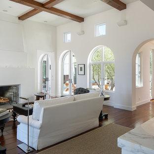 Mediterranes Wohnzimmer mit weißer Wandfarbe, braunem Holzboden, Kamin und braunem Boden in San Diego