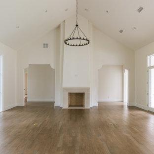 ダラスの巨大なトランジショナルスタイルのおしゃれなLDK (白い壁、無垢フローリング、標準型暖炉、コンクリートの暖炉まわり、壁掛け型テレビ、茶色い床) の写真