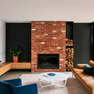 This is an example of a mid-sized contemporary open concept living room with concrete floors, a standard fireplace, a brick fireplace surround, grey floor, black walls and planked wall panelling.