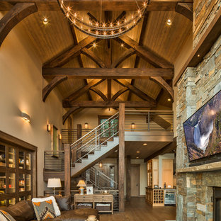 Example of a mountain style open concept medium tone wood floor and brown floor living room design in Other with beige walls, a standard fireplace, a stone fireplace and a wall-mounted tv