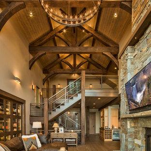 他の地域のラスティックスタイルのおしゃれなLDK (ベージュの壁、無垢フローリング、標準型暖炉、石材の暖炉まわり、壁掛け型テレビ、茶色い床) の写真