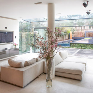 This is an example of a medium sized modern formal open plan living room in London with grey walls, a wall mounted tv and beige floors.