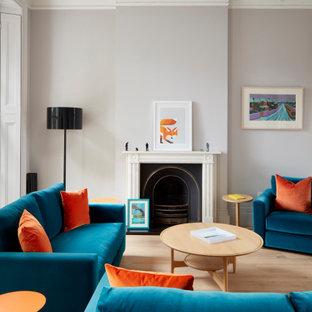 Imagen de salón para visitas abierto y abovedado, contemporáneo, grande, sin televisor, con paredes grises, suelo de madera clara, chimenea tradicional, marco de chimenea de piedra y suelo marrón