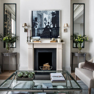Inspiration for a classic formal living room with white walls, medium hardwood flooring, a standard fireplace and brown floors.