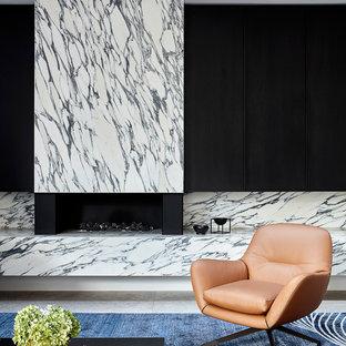 メルボルンの大きいモダンスタイルのおしゃれなリビング (ライムストーンの床、標準型暖炉、石材の暖炉まわり、内蔵型テレビ、グレーの床) の写真