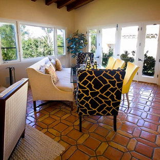 Foto di un ampio soggiorno classico aperto con angolo bar, pareti bianche, pavimento in terracotta, camino classico, cornice del camino in intonaco, nessuna TV e pavimento marrone
