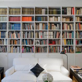 Idéer för funkis vardagsrum, med ett bibliotek, vita väggar och ljust trägolv