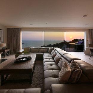 Foto de salón para visitas abierto, marinero, con suelo de madera clara, chimenea lineal y paredes beige