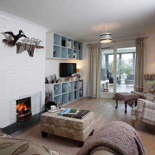 コーンウォールの小さいビーチスタイルのおしゃれなLDK (白い壁、無垢フローリング、標準型暖炉、レンガの暖炉まわり、壁掛け型テレビ) の写真