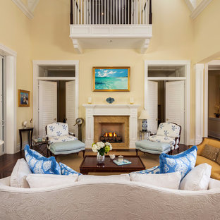 Example of an island style living room design in Miami with beige walls and a standard fireplace