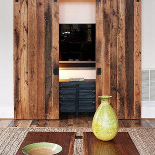 Foto di un soggiorno stile rurale con pareti bianche, pavimento in legno massello medio e TV nascosta