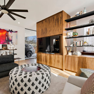Example of a large trendy open concept light wood floor and beige floor living room design in Austin with white walls, no fireplace and a wall-mounted tv