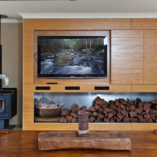 Inspiration for a tropical living room remodel in Brisbane with a wall-mounted tv and a wood stove
