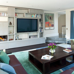 This is an example of a contemporary living room in London with beige walls, dark hardwood flooring, a ribbon fireplace and a built-in media unit.