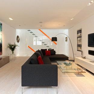 ロンドンの中くらいのモダンスタイルのおしゃれなリビング (白い壁、横長型暖炉、漆喰の暖炉まわり、埋込式メディアウォール、白い床) の写真
