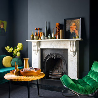 Example of a trendy formal living room design in London with black walls and a standard fireplace