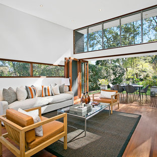 Photo of a contemporary living room in Sydney with white walls, medium hardwood floors and a standard fireplace.