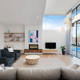 This is an example of a contemporary living room in Melbourne with white walls, light hardwood floors, a freestanding tv and beige floor.