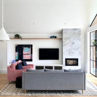 Idées déco pour un salon contemporain ouvert avec un mur blanc, un sol en bois clair, une cheminée standard, un téléviseur fixé au mur, un sol beige et un plafond voûté.