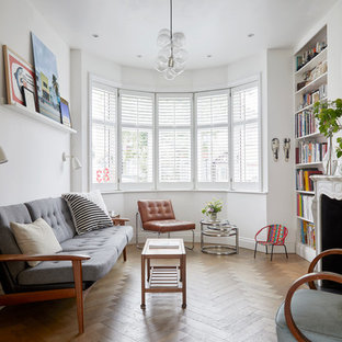 Eclectic enclosed living room in London with white walls, medium hardwood flooring, a standard fireplace, no tv and brown floors.