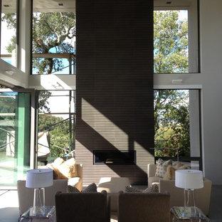 Idee per un grande soggiorno minimalista aperto con sala formale, pareti grigie, pavimento con piastrelle in ceramica, camino classico, cornice del camino piastrellata e TV nascosta