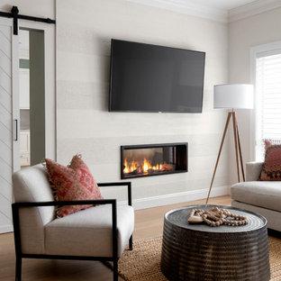 Bild på ett mellanstort vintage vardagsrum, med beige väggar, mellanmörkt trägolv, en dubbelsidig öppen spis, en spiselkrans i metall, en väggmonterad TV och beiget golv