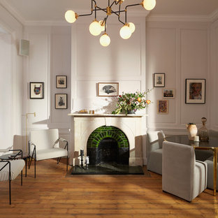 Design ideas for a traditional living room in London with white walls, medium hardwood flooring, a standard fireplace, a tiled fireplace surround, no tv and brown floors.