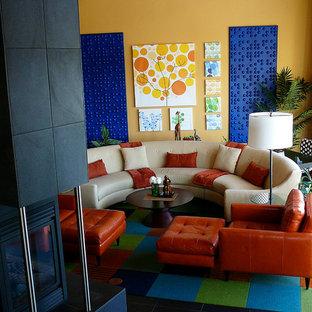 Esempio di un grande soggiorno contemporaneo aperto con pavimento in gres porcellanato, camino bifacciale, cornice del camino piastrellata, parete attrezzata e pareti gialle