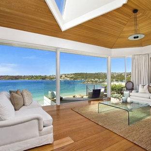 Immagine di un soggiorno tropicale con pareti bianche, pavimento in legno massello medio, nessun camino e nessuna TV
