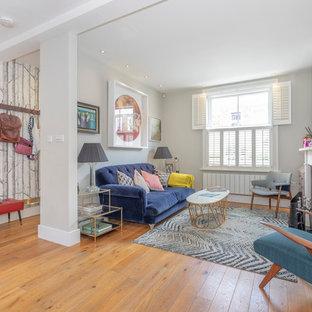 Imagen de salón cerrado, contemporáneo, de tamaño medio, con paredes grises y suelo de madera clara