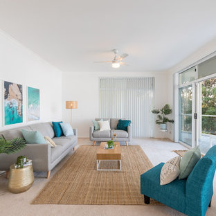 Mid-sized beach style living room in Other with white walls, carpet and beige floor.