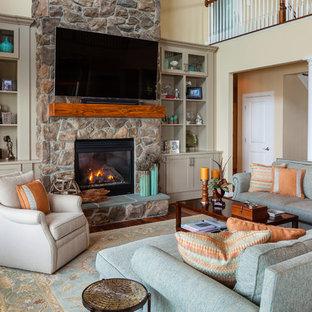 ボルチモアのビーチスタイルのおしゃれなLDK (黄色い壁、濃色無垢フローリング、標準型暖炉、石材の暖炉まわり、壁掛け型テレビ、茶色い床) の写真