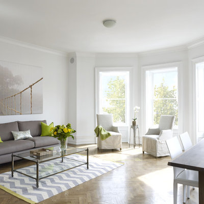 Example of a large trendy open concept medium tone wood floor and brown floor living room design in New York with white walls, no tv and no fireplace