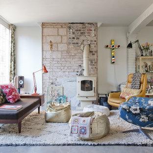 Imagen de salón para visitas cerrado, ecléctico, grande, sin televisor, con paredes blancas, suelo de cemento y estufa de leña