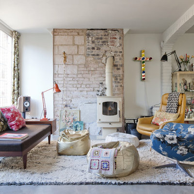 Living room - large eclectic formal and enclosed concrete floor living room idea in Barcelona with white walls, a wood stove and no tv