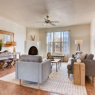 Esempio di un soggiorno american style di medie dimensioni e aperto con pareti bianche, pavimento in terracotta, camino ad angolo, cornice del camino in intonaco, nessuna TV e pavimento arancione